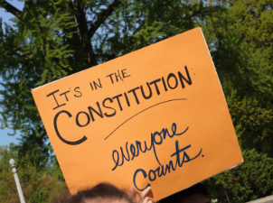 "Orange sign that says ""It's in the Constitution: Everyone Counts"""